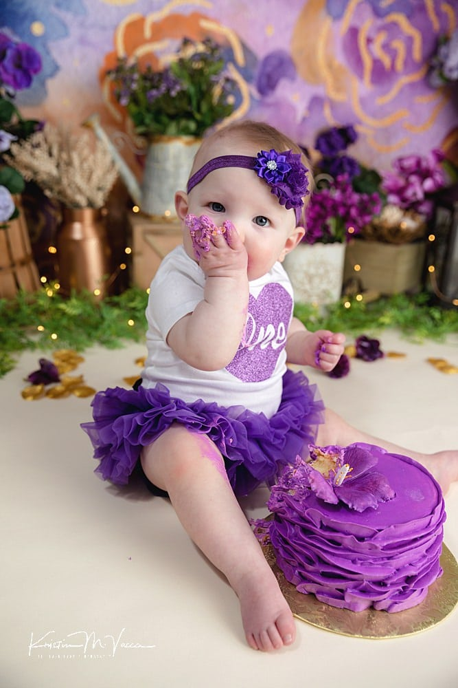 Purple floral cake smash by The Flash Lady Photography.